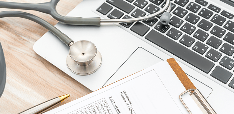 Electronic Health Records: a laptop with a stethoscope and paper records nearby