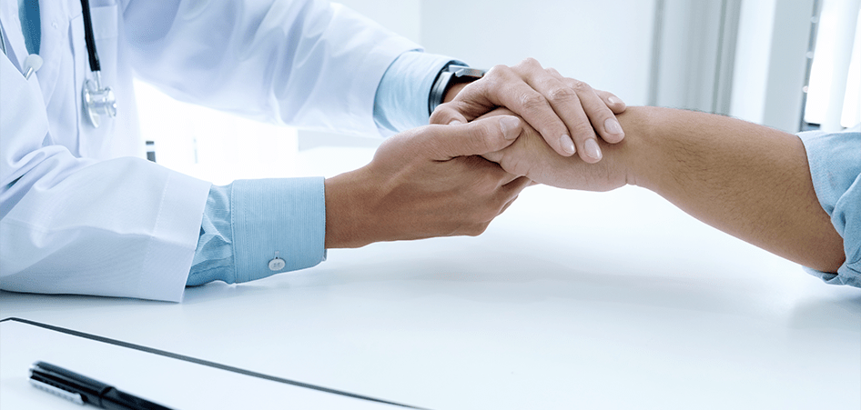 eHealth for patient engagement: a doctor's hand holding a patient's hand while comforting