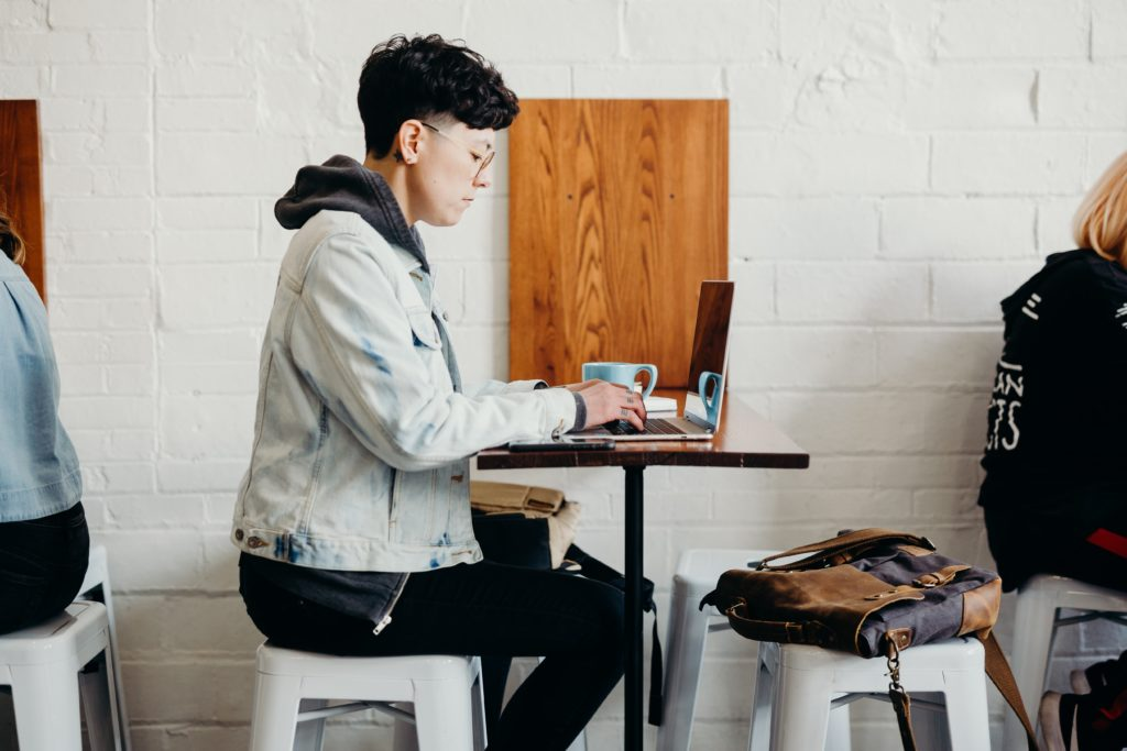 Remote team worker sitting in a cafe with a laptop