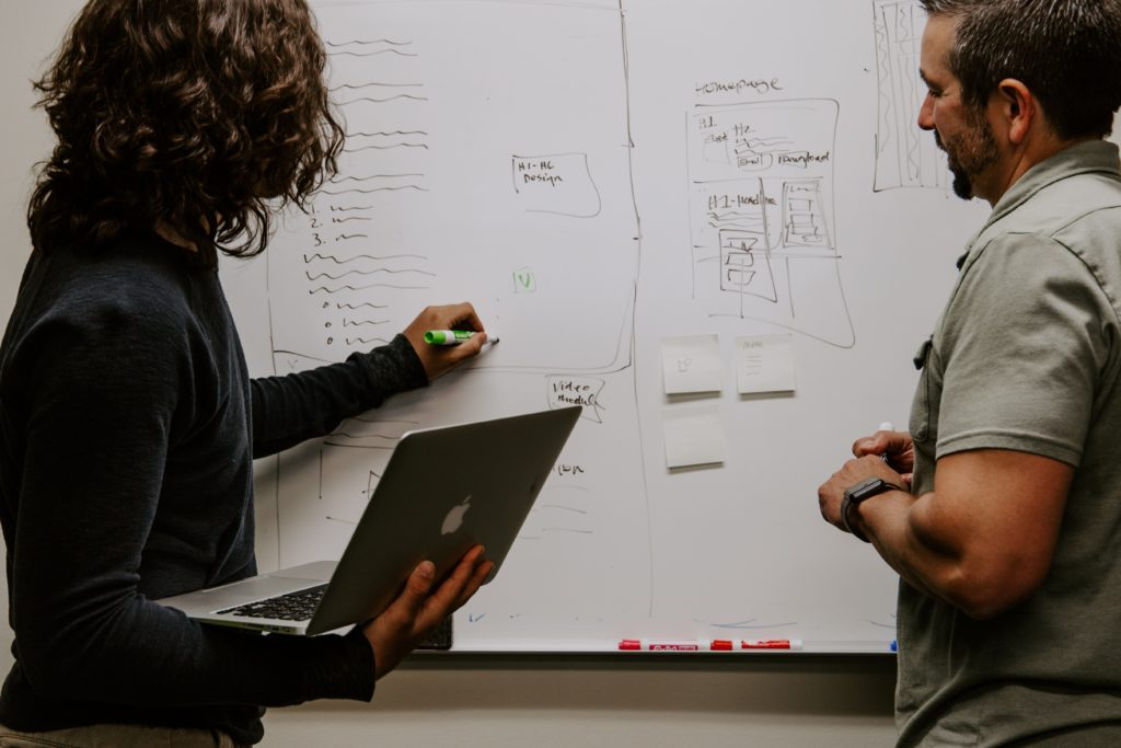 Two people doing business analysis using a whiteboard