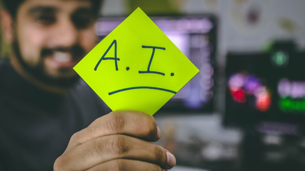 A man holding a green note AI written on it