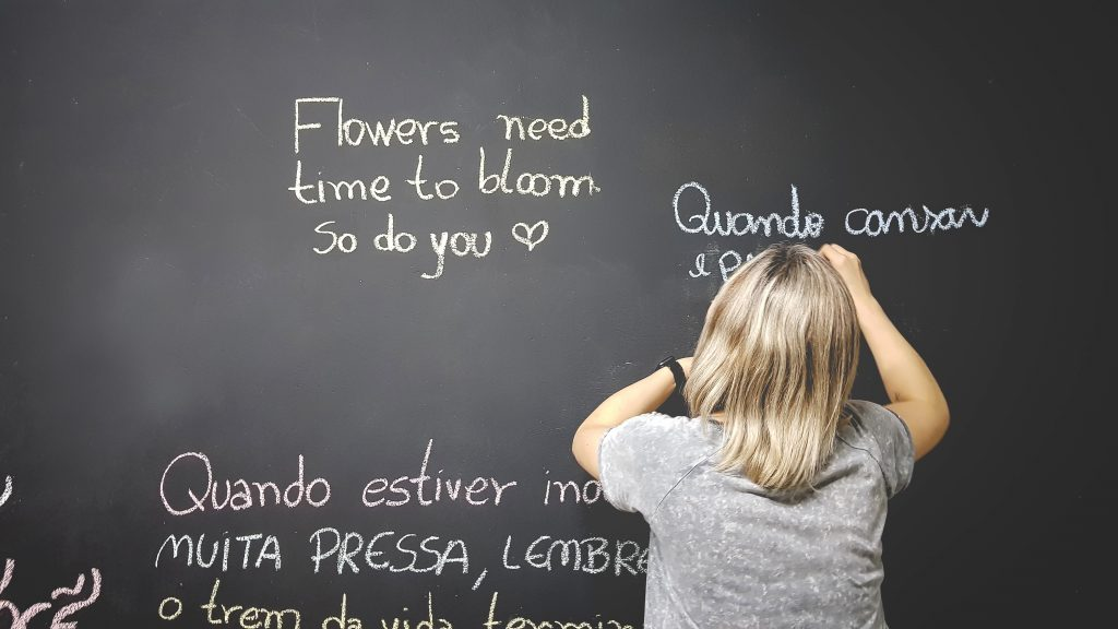 Language learning applications, a person writes on a blackboards with white chalk in different languages
