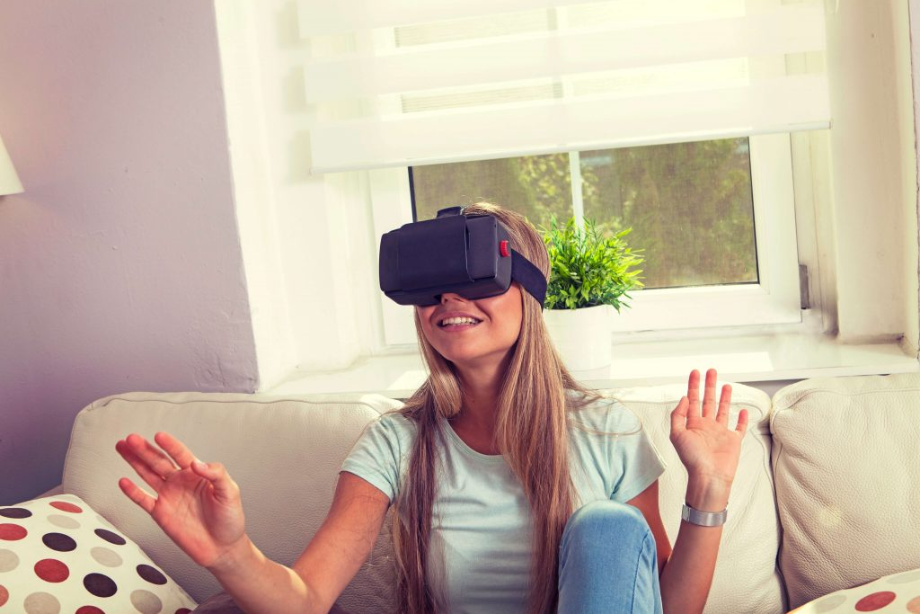 A young woman wearing a VR headset and enjoying gaming