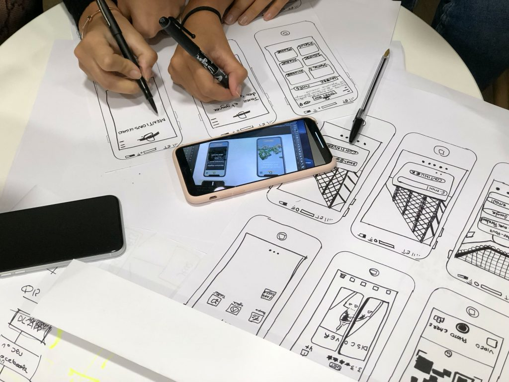 A group of people is planning to build an app using hand drawings for prototyping.