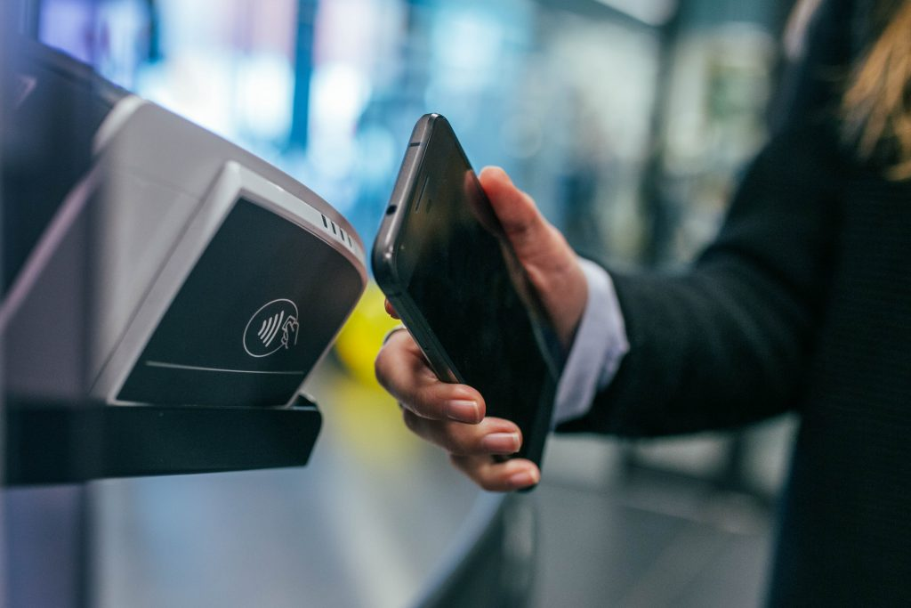 A woman using a Security in Fintech solution of contactless payment with a cell phone