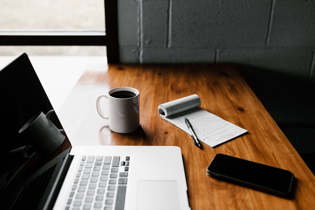 Outsourcing can help businesses to deal with the post-COVID recession: remote worker's station with a laptop and other devices.