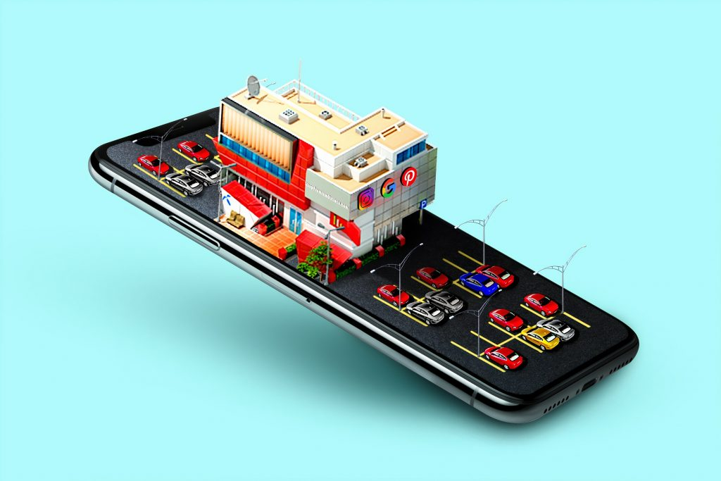 When adapting business models to digitalization make sure your business is discoverable on the internet: a 3D model of a brick-and-mortar shop over the mobile screen.