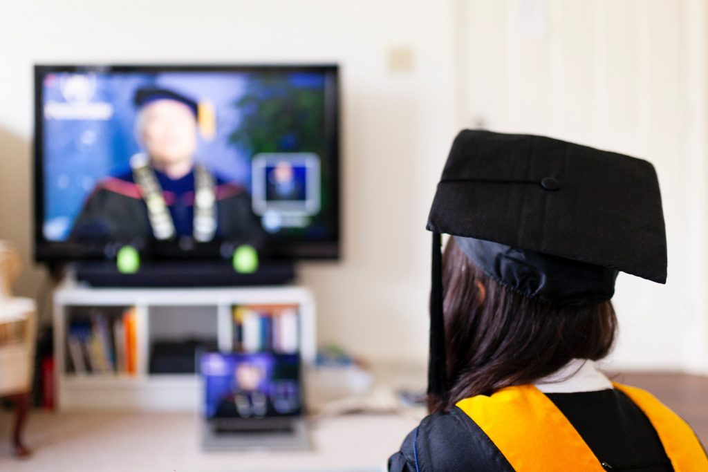 Learning Management System: a graduate listens to a professor speaking through a video conference