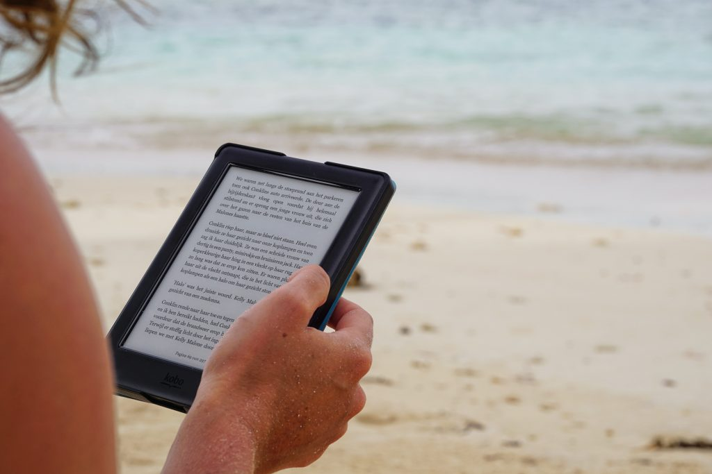 Learning management system features: a person reading an e-book on a beach